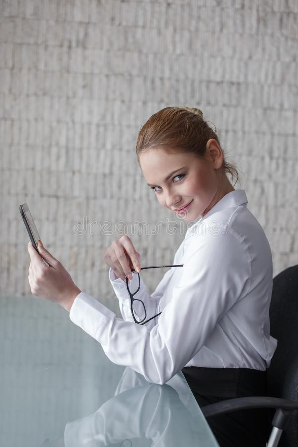 Young smart businesswoman holding tablet and eyeglasses royalty free stock photos