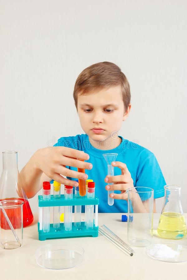 Young smart chemist doing chemical experiments in laboratory. Young smart chemist doing chemical experiments in the laboratory stock photo