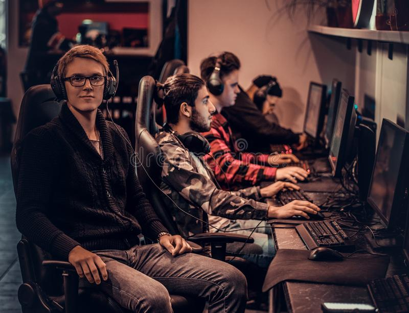 A young smart gamer wearing a sweater and glasses sitting on a gamer chair and looking at a camera in a gaming club or. A smart gamer wearing a sweater and stock images