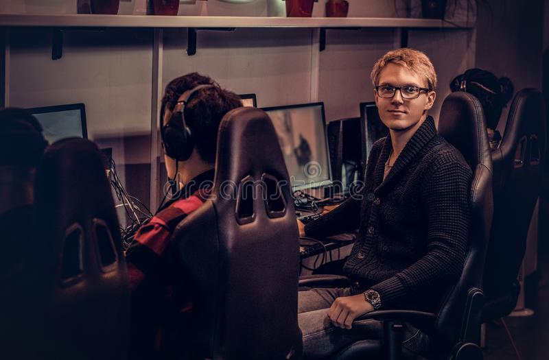A young smart gamer wearing a sweater and glasses sitting on a gamer chair and looking at a camera in a gaming club or. A smart gamer wearing a sweater and stock photos