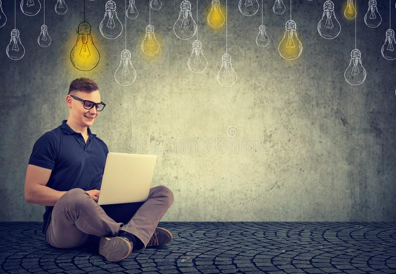 Intelligent young man with laptop stock photography