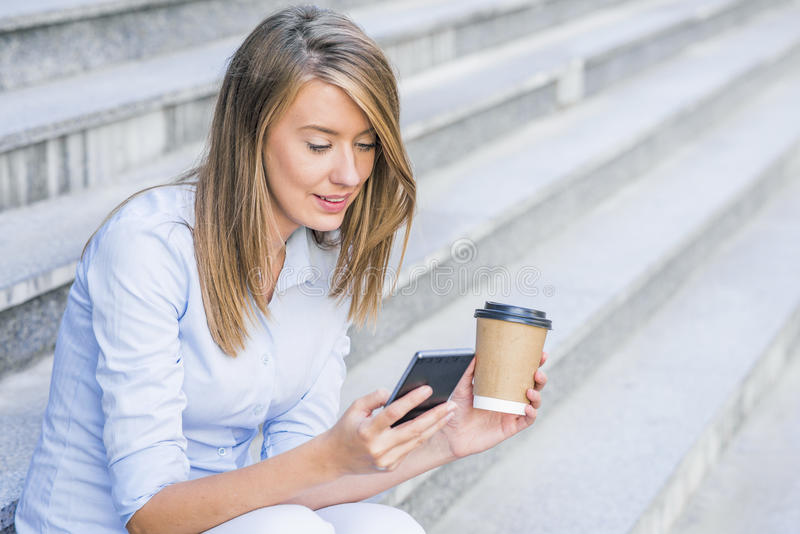 Young smart professional woman reading using phone. Female businesswoman reading news or texting sms on smartphone while drinking. Coffee on break from work royalty free stock images
