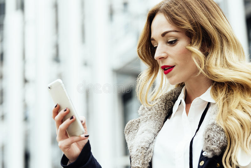 Young smart professional woman reading using phone. stock photo