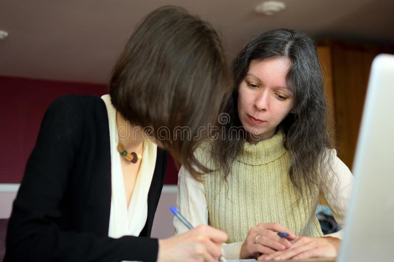Young smartly dressed lady helps another young lady to work with documents, fill forms and sign stock image