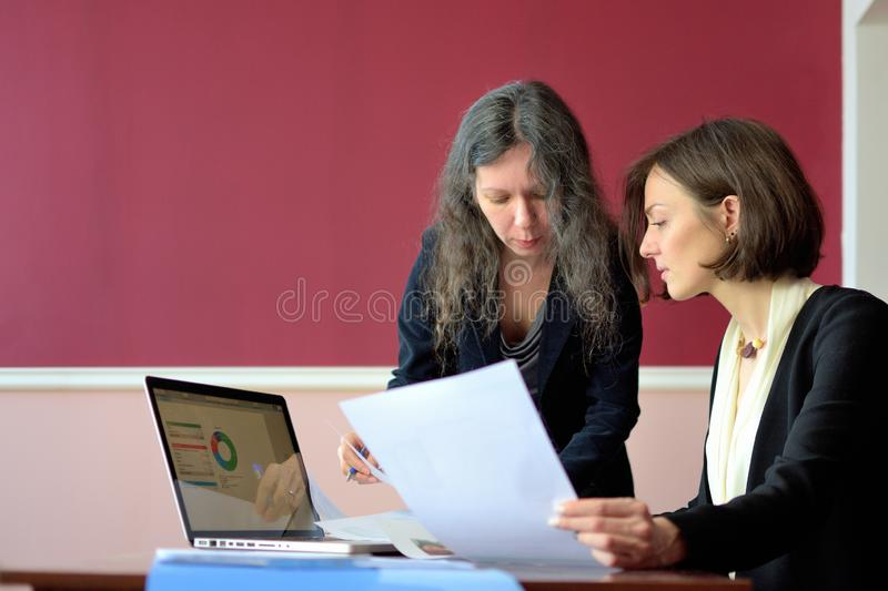 Young smartly dressed lady helps another young lady to work with documents, fill forms and sign royalty free stock photography