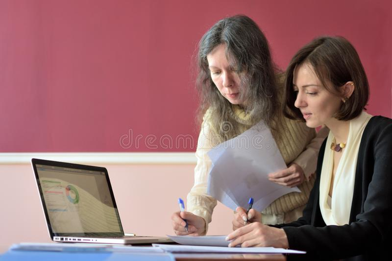 Young smartly dressed lady helps another young lady to work with documents, fill forms and sign royalty free stock photos