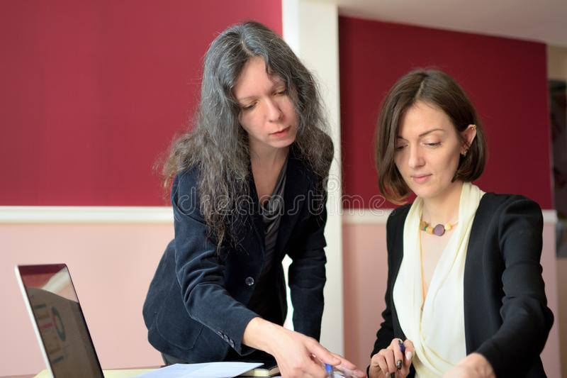 Young smartly dressed lady helps another young lady to work with documents, fill forms and sign royalty free stock image