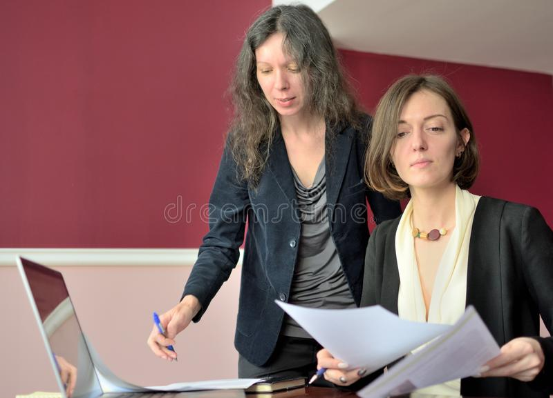 Young smartly dressed lady helps another young lady to work with documents, fill forms and sign stock images