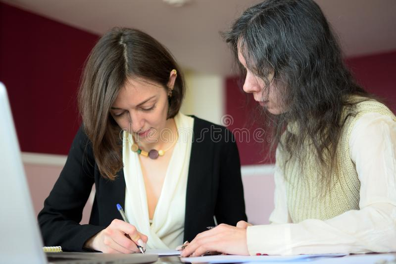 Young smartly dressed lady helps another young lady to work with documents, fill forms and sign royalty free stock photo