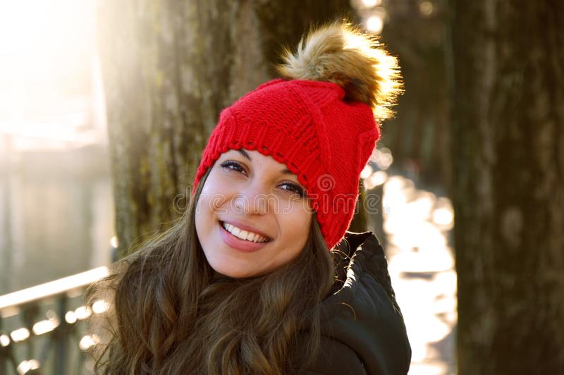 Young Smile winter young woman portrait. Beauty joywoman looking to the side outdoor in a sunny day with flare and city background stock images