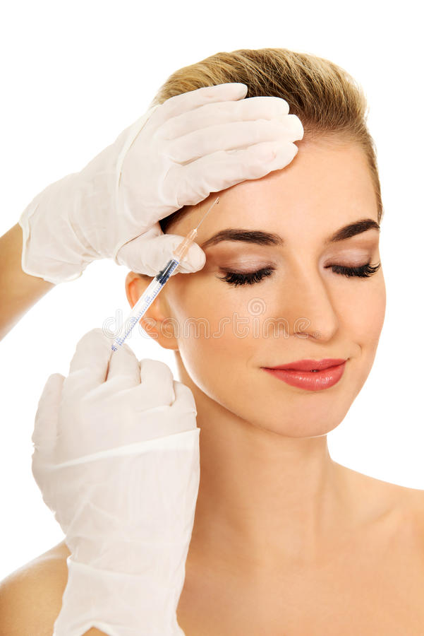 Young smiled woman is having facial botox injection. stock image