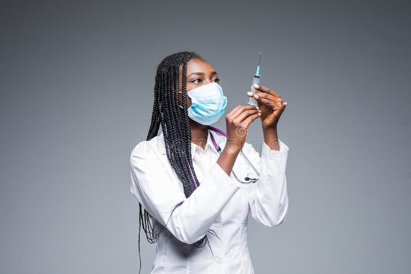 Young smiling African American doctor in medical mask holding a syringe isolated on gray stock images