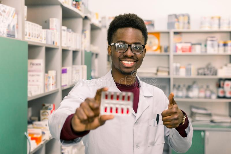 Young smiling African American man pharmacist holding red pills blister in hand while standing in interior of modern stock photos