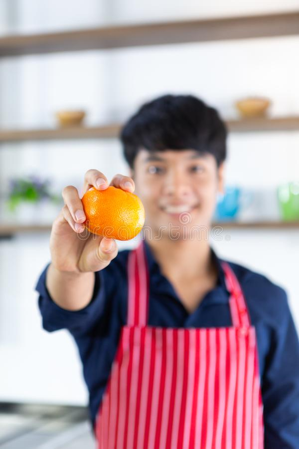 Young smiling asian man with red apron showing orange in right hand on wooden shelf background stock photos