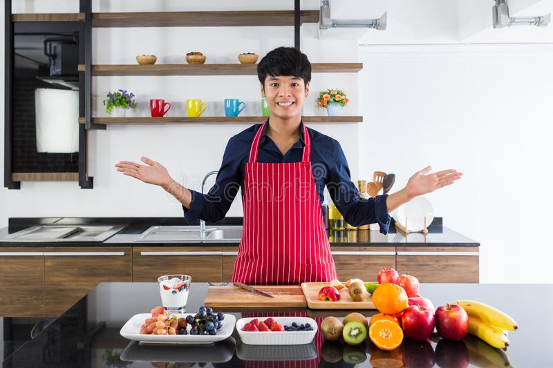 Young smiling asian man showing hand present assorted fruits on black wooden table stock photo