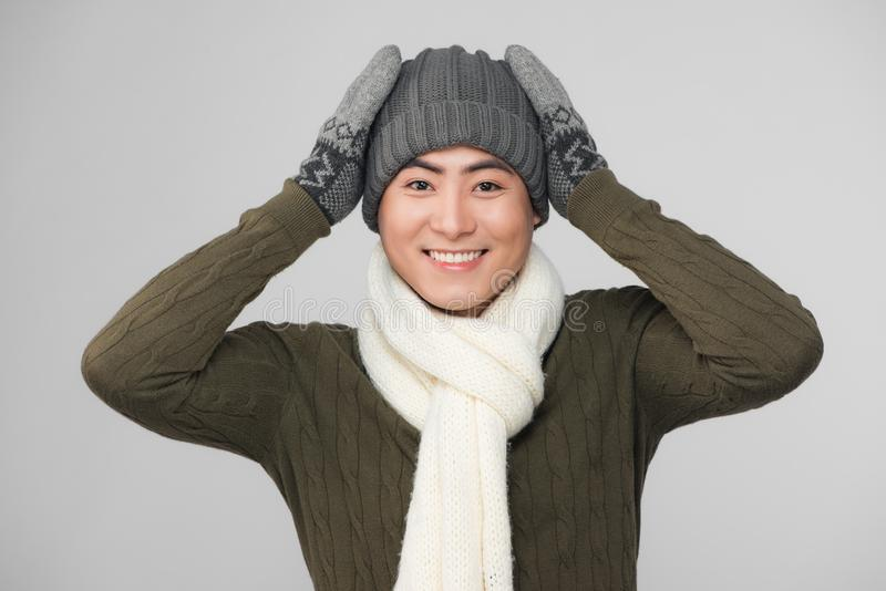 Young smiling asian man wearing knitted sweater and gloves stock photography