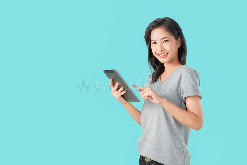 Young smiling Asian woman holding digital tablet with pointing finger on light blue background. stock photography