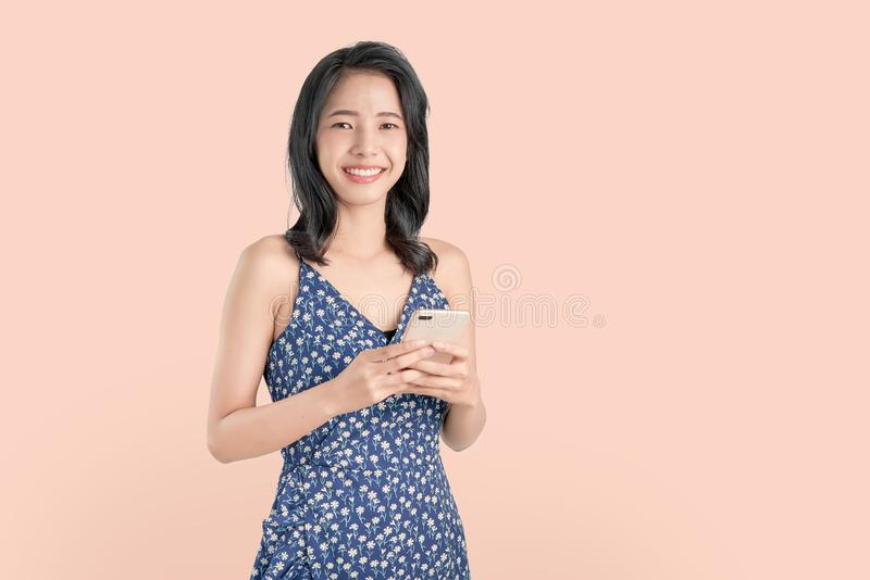 Young smiling Asian woman holding smartphone isolated on light pink background. royalty free stock photos