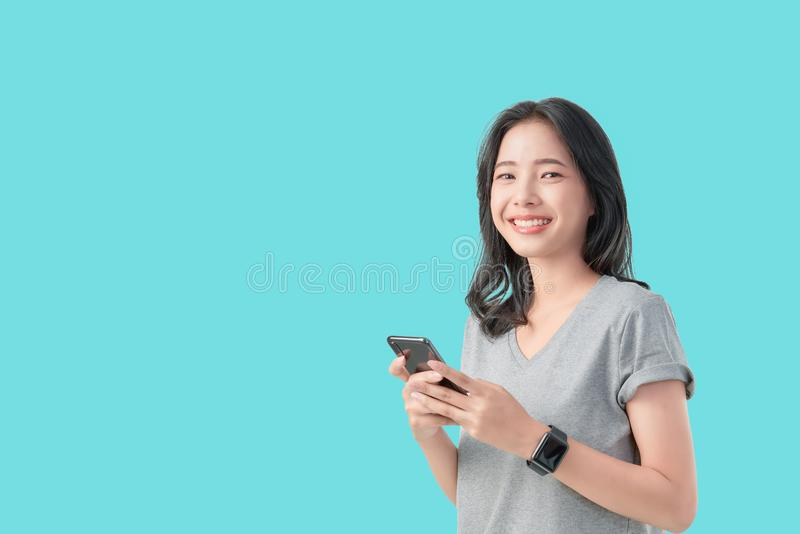 Young smiling Asian woman holding smartphone and wear smartwatch isolated on light blue background. royalty free stock photo