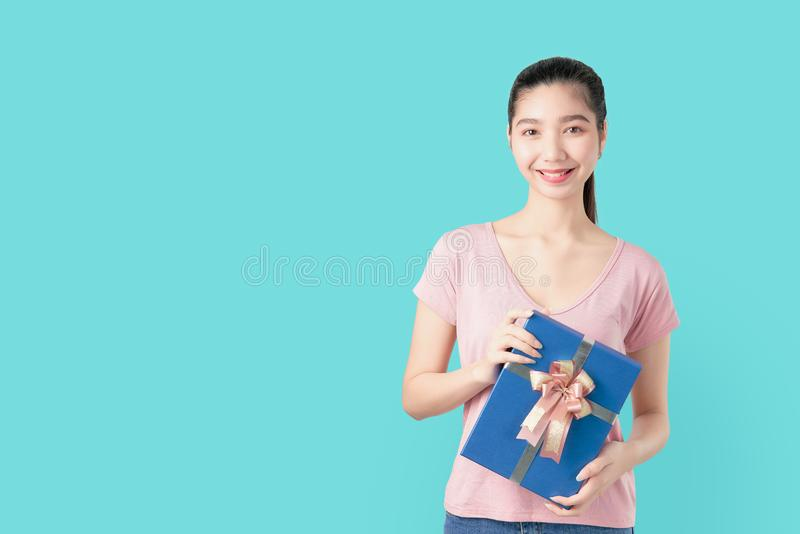 Young smiling Asian woman in pink t-shirt holding blue gift on light background. royalty free stock photo