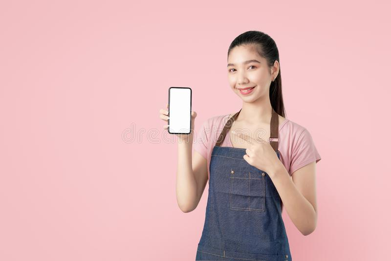 Young smiling Asian woman show smartphone blank screen with pointing finger on light pink background. royalty free stock photo