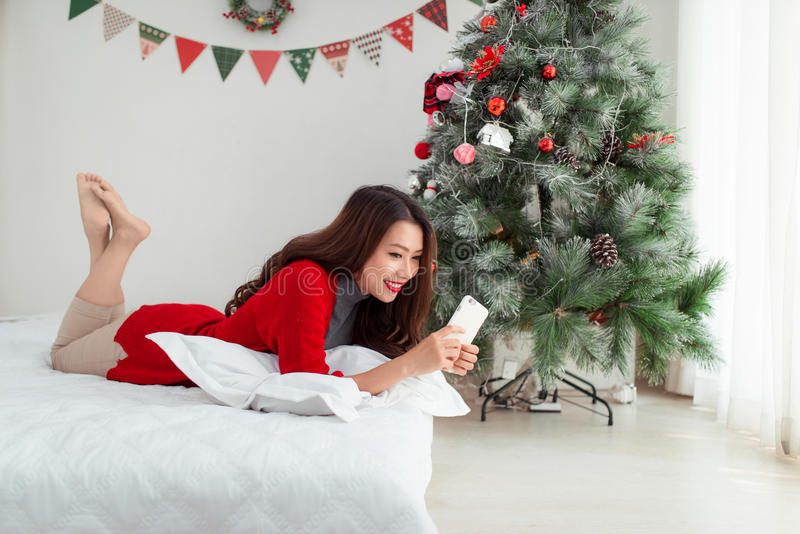 Young smiling asian woman is using mobile phone. Christmas and N stock photography