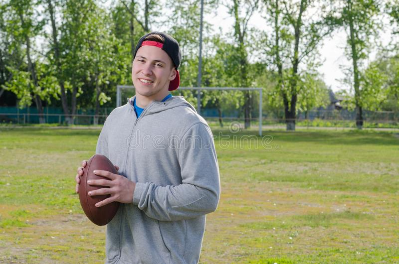 Young smiling athlete holding a football ball royalty free stock photo
