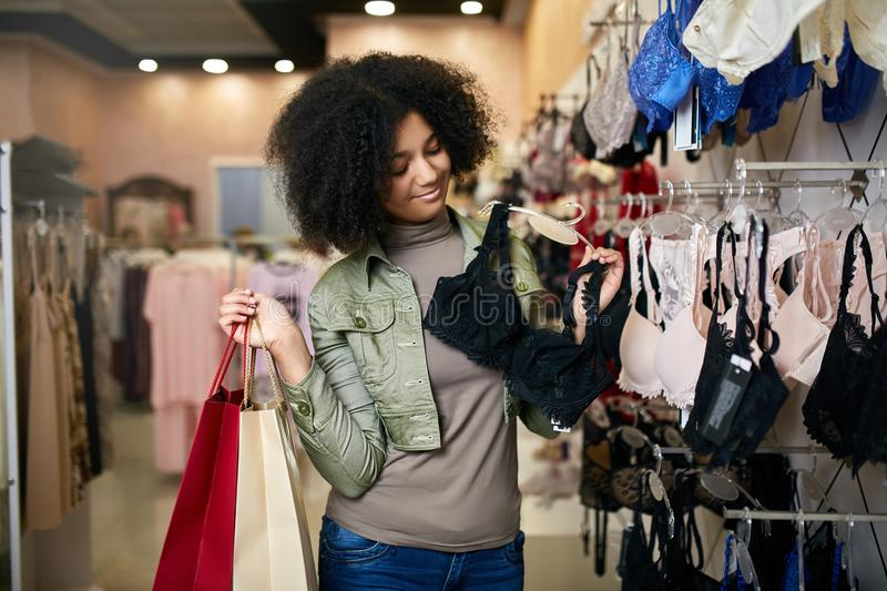 Young smiling attractive african american woman choosing right bra size in lingerie store boutique. Black mixed race stock images