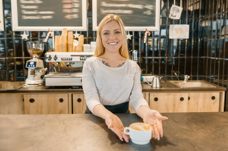 Young smiling barista girl with cup of freshly prepared coffee. Blond woman in an apron, near the bar counter in coffee shop stock photography