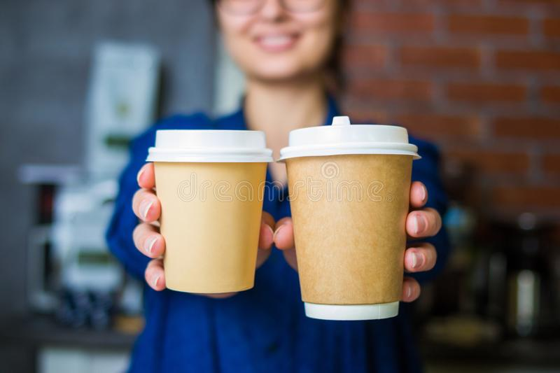 Young smiling barista girl holds out her hands with a paper cups of coffee. To go with space for logo stock images