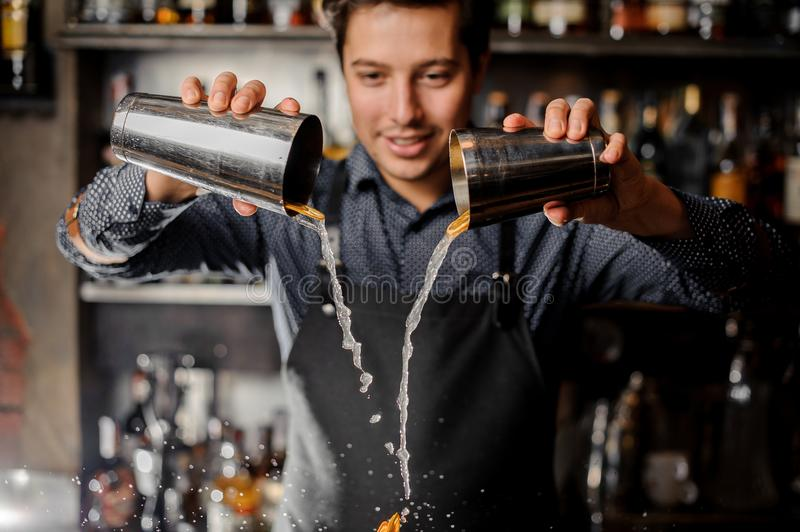Young smiling barman pouring drink with slices of fresh orange fruit stock photography