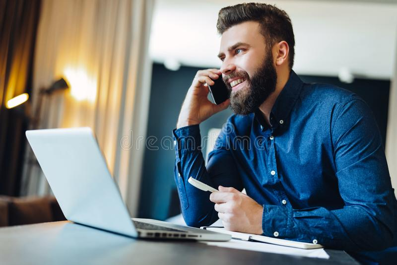 Young smiling bearded businessman sitting in front of computer, talking on cell phone, holding pen. Phone conversations. royalty free stock photo