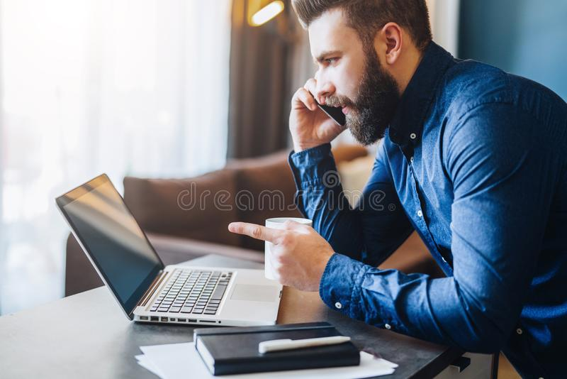 Young bearded businessman is sitting at table in front of computer,talking on cell phone,showing finger on laptop screen. Young smiling bearded businessman is royalty free stock photos
