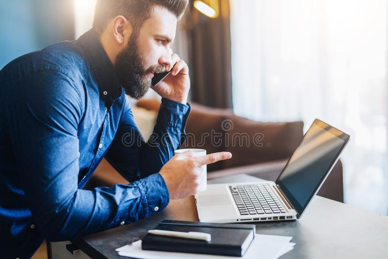 Young bearded businessman is sitting at table in front of computer,talking on cell phone,showing finger on laptop screen. Young smiling bearded businessman is royalty free stock photography
