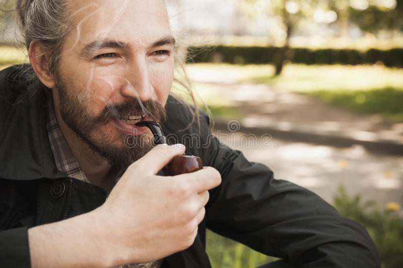 Young smiling bearded man smoking pipe. Young smiling asian bearded man smoking pipe in summer park, close up portrait royalty free stock images