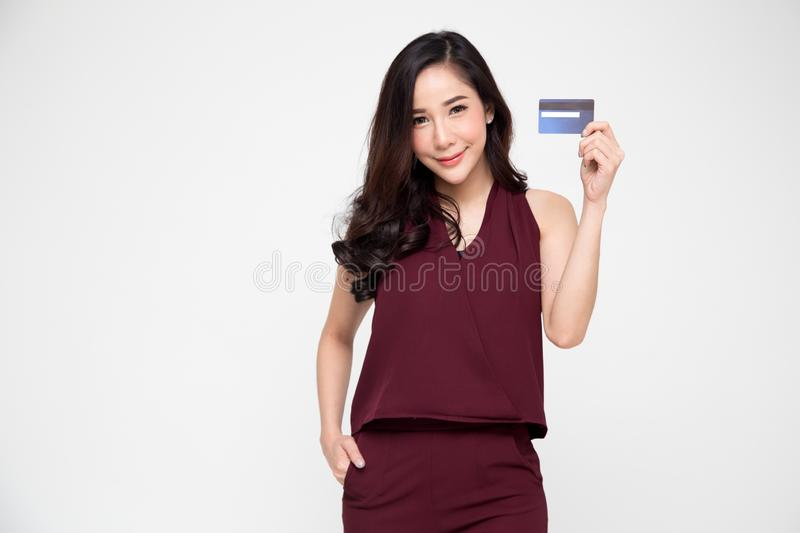 Young smiling beautiful Asian woman presenting credit card in hand for making payment shopping royalty free stock photo