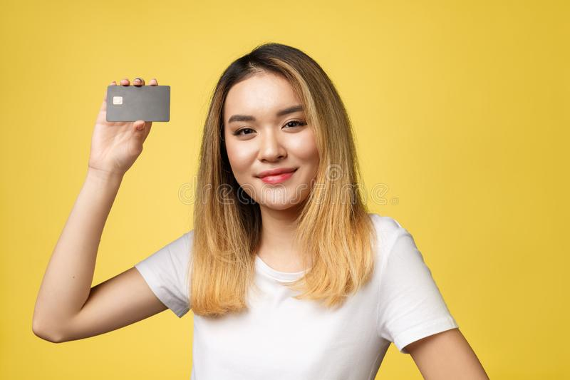 Young smiling beautiful Asian woman presenting credit card in hand showing trust and confidence for making payment. stock photography