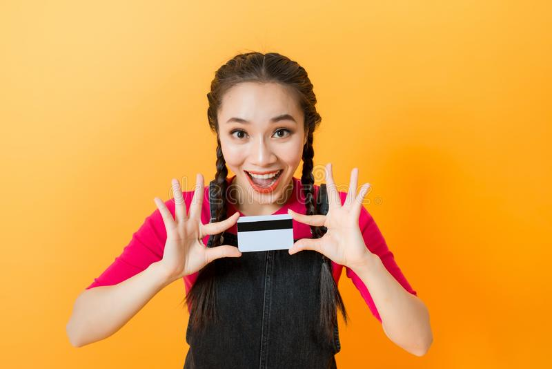 Young smiling beautiful Asian woman presenting credit card in hand showing trust and confidence for making payment stock images