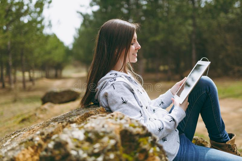 Young smiling beautiful woman in casual clothes with earphones sitting on stone using tablet pc computer in city park or. Forest on green blurred background royalty free stock photography