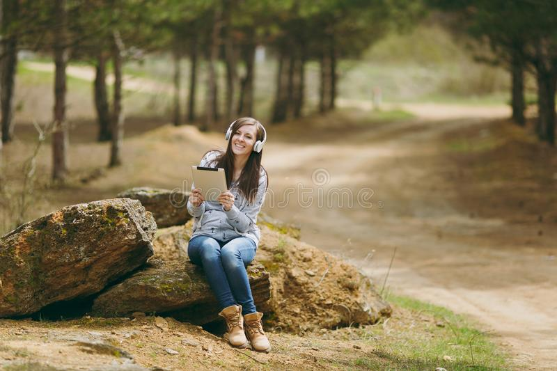 Young smiling beautiful woman in casual clothes with headphones sitting on stone using tablet pc computer in city park. Or forest on green blurred background stock image