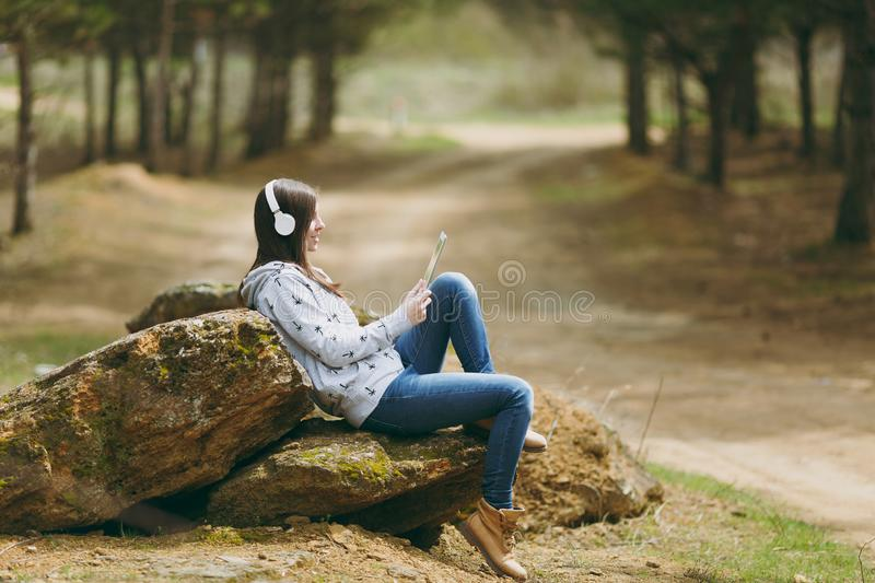 Young smiling beautiful woman in casual clothes with headphones sitting on stone using tablet pc computer in city park. Or forest on green blurred background royalty free stock images
