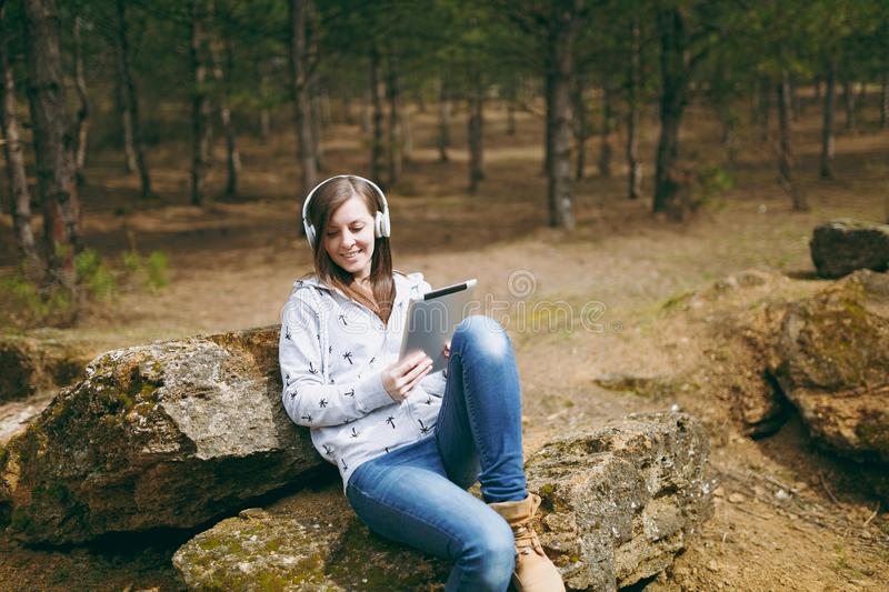 Young smiling beautiful woman in casual clothes with headphones sitting on stone using tablet pc computer in city park. Or forest on green blurred background stock photo
