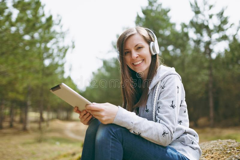 Young smiling beautiful woman in casual clothes with headphones sitting on stone using tablet pc computer in city park. Or forest on green blurred background royalty free stock photo