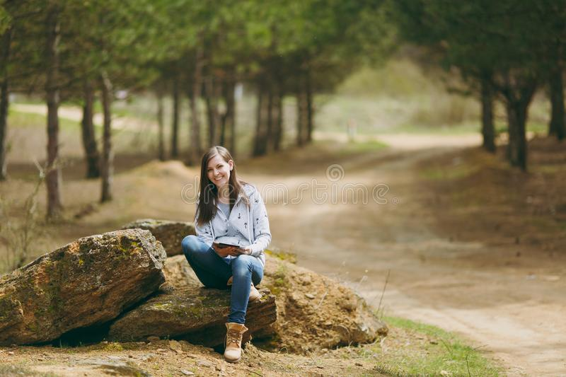 Young smiling beautiful woman in casual clothes sitting on stone cross-legged using tablet pc computer in park or forest. On green blurred background. Student stock photography
