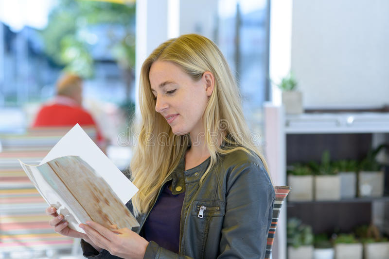 Young blond woman reading menu. Young smiling blond woman reading the menu while sitting in a restaurant royalty free stock photography