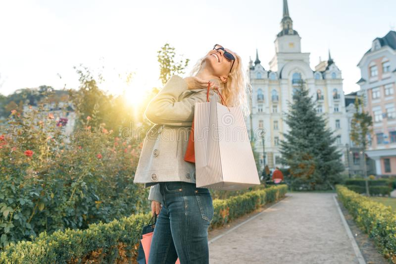 Young smiling blonde woman with curly hair with bags for shopping, sunny city background, golden hour.  royalty free stock image