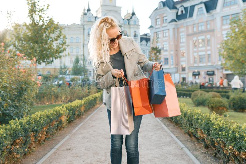 Young smiling blonde woman with curly hair with bags for shopping, sunny city background, golden hour.  stock photos