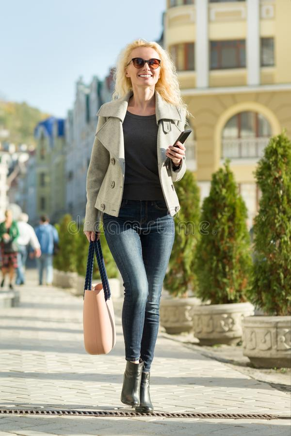Young smiling blonde woman with curly hair with smartphone in her hands walking on a city street, autumn sunny day.  stock photo