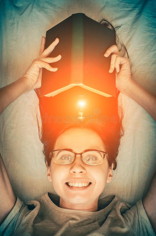 Young smiling girl with a book and a glowing bulb as a concept of inspiration. Young smiling brunette girl with a book and a glowing bulb as a concept of royalty free stock images