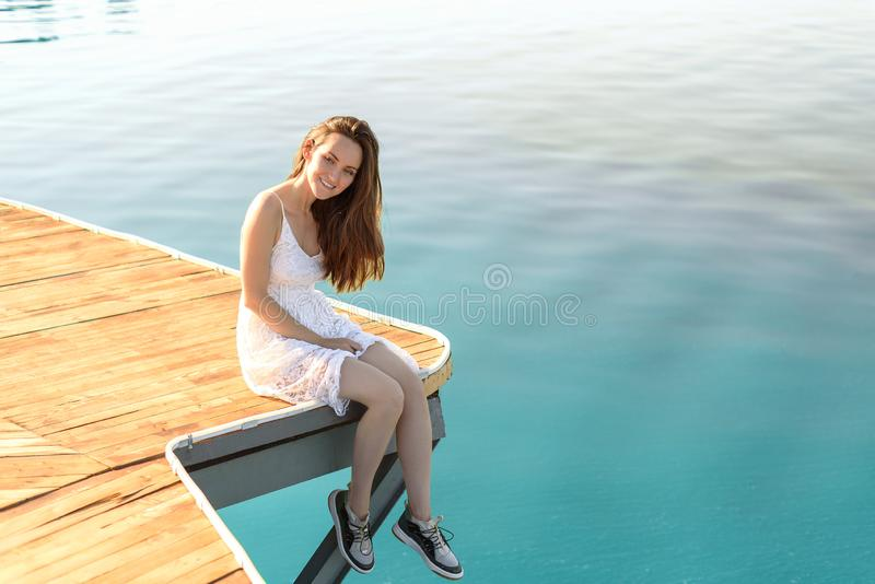 Young smiling brunette in white dress sitting on a wooden pier against the azure sea looks away, sunbathing at sunset of the day stock photos